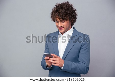 Portrait of a happy businessman using smartphone over gray background - stock photo
