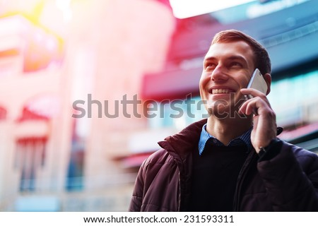 Portrait of a happy businessman walking outdoors with mobile phone. Man with phone. Happy man talking phone. Man walking with phone. Man outdoor with phone. Businessman outdoor with phone. - stock photo