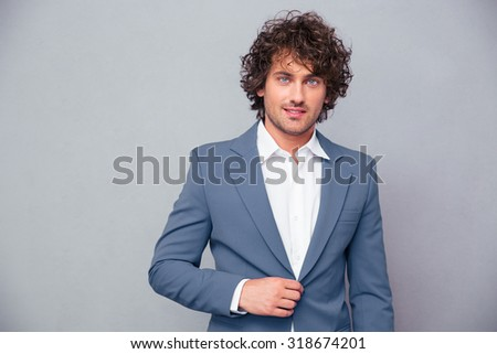 Portrait of a happy businessman with curly hair looking at camera over gray background - stock photo