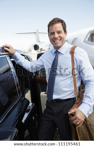 Portrait of a happy businessman with luggage by the car at airfield - stock photo