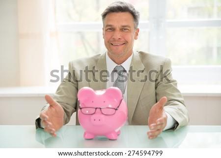 Portrait Of A Happy Businessman With Piggybank Wearing Eyeglasses On Desk - stock photo