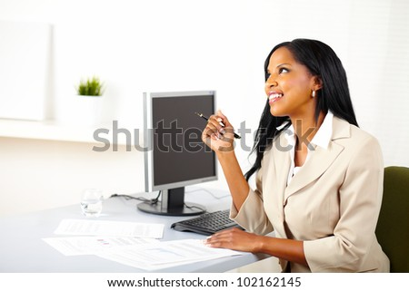 Portrait of a happy businesswoman on work desk, smiling and looking up