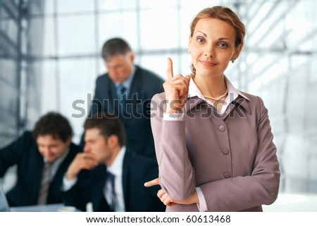 Portrait of a  happy businesswoman pointing upwards with her colleagues at the background. - stock photo
