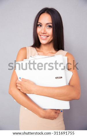 Portrait of a happy businesswoman standing with folders over gray background and looking at camera - stock photo