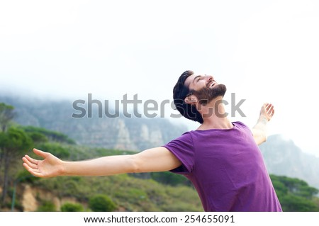 Portrait of a happy carefree man smiling with arms open outdoors - stock photo