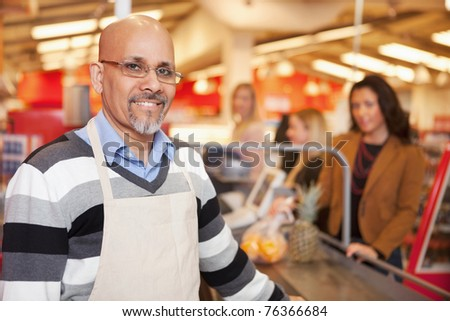 Portrait of a happy cashier with customer in the background - stock photo
