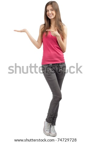 Portrait of a happy casual girl showing something on the palm of her hand and pointing, against white background - stock photo