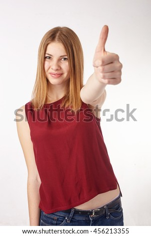 Portrait of a happy casual girl showing thumbs up and smiling, against white background - stock photo