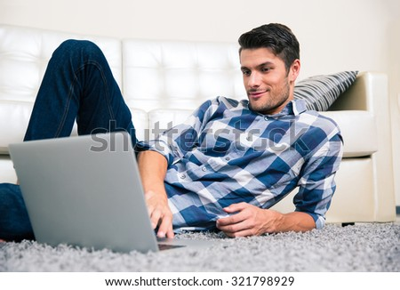 Portrait of a happy casual man using laptop on the floor at home - stock photo