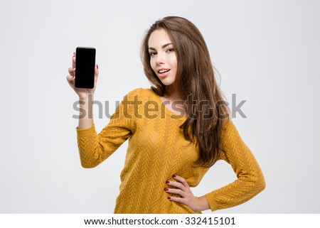 Portrait of a happy casual woman showing blank smartphone screen isolated on a white background - stock photo