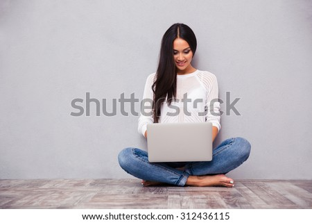 Portrait of a happy casual woman sitting on the floor with laptop on gray background - stock photo