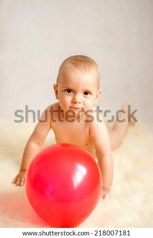 portrait of a happy caucasian adorable baby boy with red balloon - stock photo