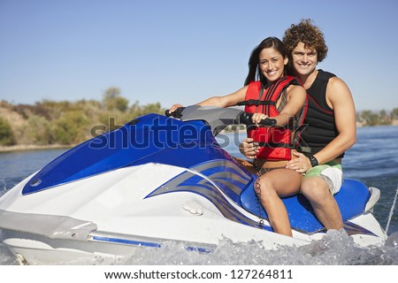 Portrait of a happy caucasian couple riding jet ski on lake - stock photo