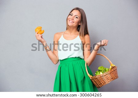 Portrait of a happy charming woman holding basket with vegetables and bagel over gray background - stock photo