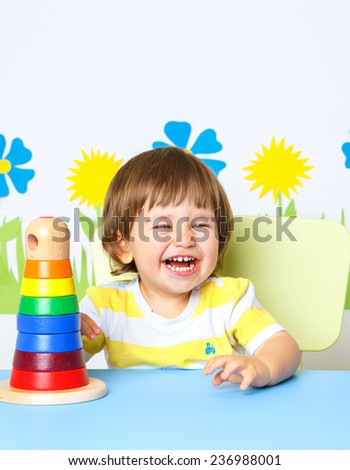 Portrait of a Happy cheerful baby at kindergarten or playgroup with bright spring colors - stock photo