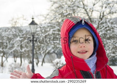 Portrait of a happy  child boy in winter in snow.