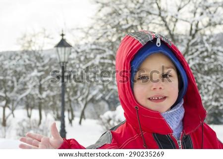 Portrait of a happy  child boy in winter in snow. - stock photo