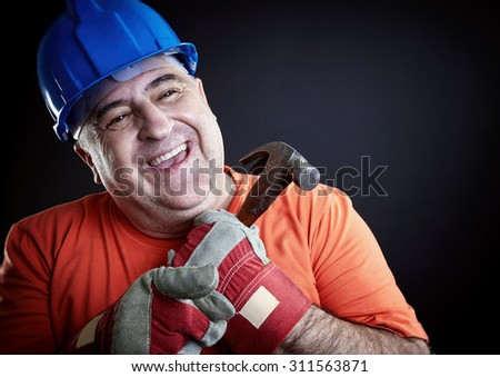 Portrait of a happy construction worker wearing safety equipment holding hammer. - stock photo
