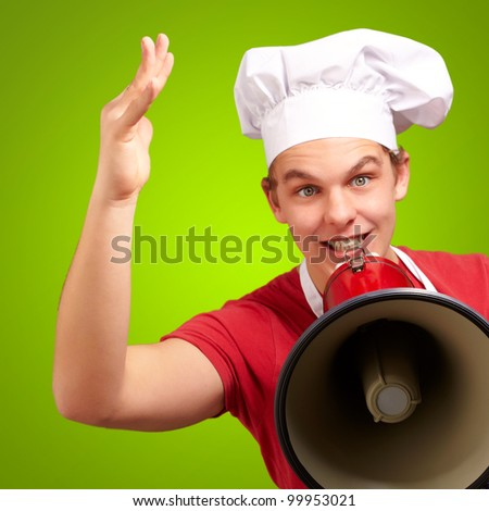portrait of a happy cook man shouting using a megaphone over a green background