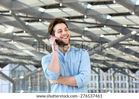 Portrait of a happy cool guy talking on mobile phone - stock photo