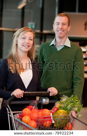 Portrait of a happy couple in a grocery store - stock photo