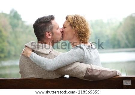 Portrait of a happy couple kissing on park bench - stock photo