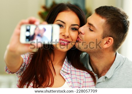 Portrait of a happy couple making selfie photo with smartphone - stock photo