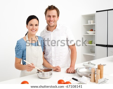 Portrait of a happy couple preparing a bolognese sauce together in the kitchen - stock photo