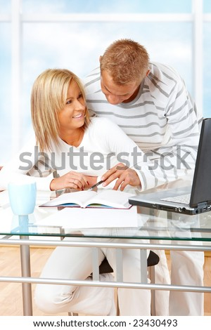 Portrait of a happy couple with laptop in home or office