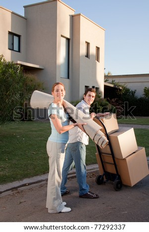 Portrait of a happy couple with moving boxes and small rug