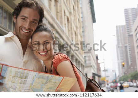 Portrait of a happy couple with road map
