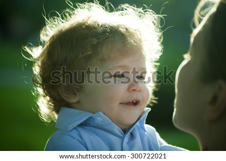 Portrait of a happy curly baby boy staring at face of his mother carefully with love outdoor closeup, horizontal photo - stock photo