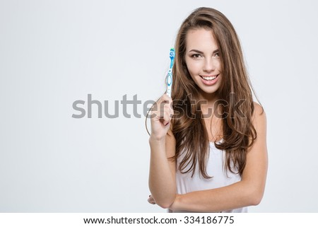 Portrait of a happy cute woman holding toothbrush isolated on a white background and looking at camera - stock photo