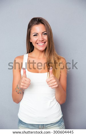 Portrait of a happy cute woman showing thumbs up over gray background. Looking at camera - stock photo