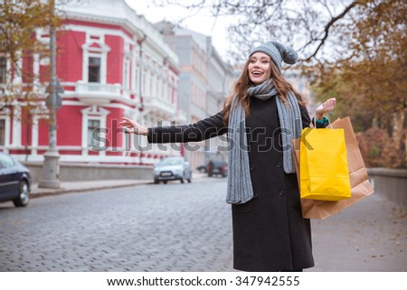 Portrait of a happy cute woman tries to stop the car on road in old european town