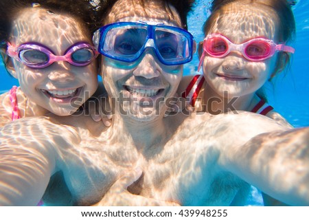 Portrait of a happy dad with two young daughters under water. Selfies - stock photo