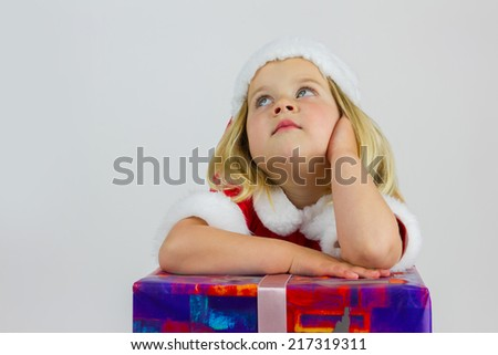 Portrait of a happy dreamer girl in red new year cap - stock photo