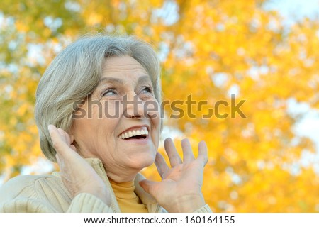 Portrait of a happy elderly woman outdoors - stock photo