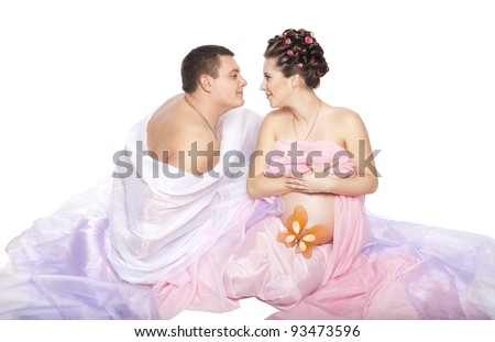 portrait of a happy embracing expecting couple with pregnant woman