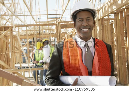 Portrait of a happy engineer holding blueprint at construction site - stock photo
