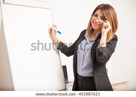 Portrait of a happy English teacher with glasses teaching a class using a flip chart - stock photo