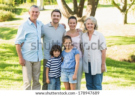Portrait of a happy extended family standing in the park - stock photo