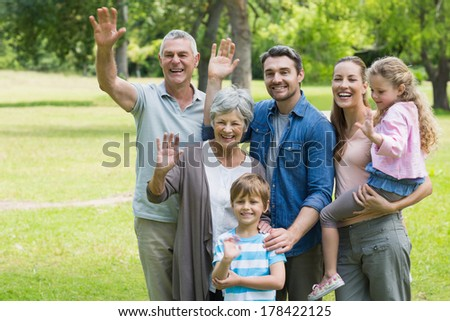 Portrait of a happy extended family waving hands at the park - stock photo