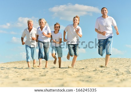 Portrait of a happy family a running barefoot in the sand in the summer - stock photo