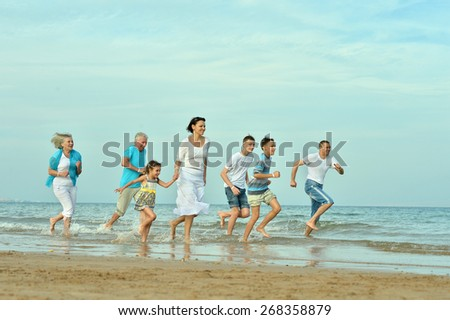 Portrait of a happy family at beach in summer with hands up - stock photo