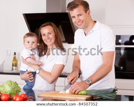 Portrait of a happy family at home in the kitchen preparing a meal - stock photo