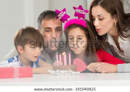 Portrait Of A Happy Family Blowing Candles On Birthday Cake Together - stock photo
