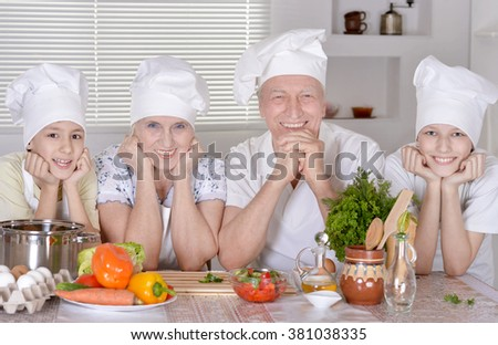 Portrait of a happy family cooking together with grandchildren - stock photo