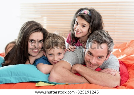 Portrait of a happy family having fun in bed They are looking at camera, laying one on top of another They are wearing casual clothes on a bright color bed. The little girl has a head band in her hair
