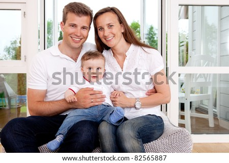 Portrait of a happy family looking at the camera in a home interior - stock photo